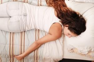 女性 疲れてベッドに倒れ込む