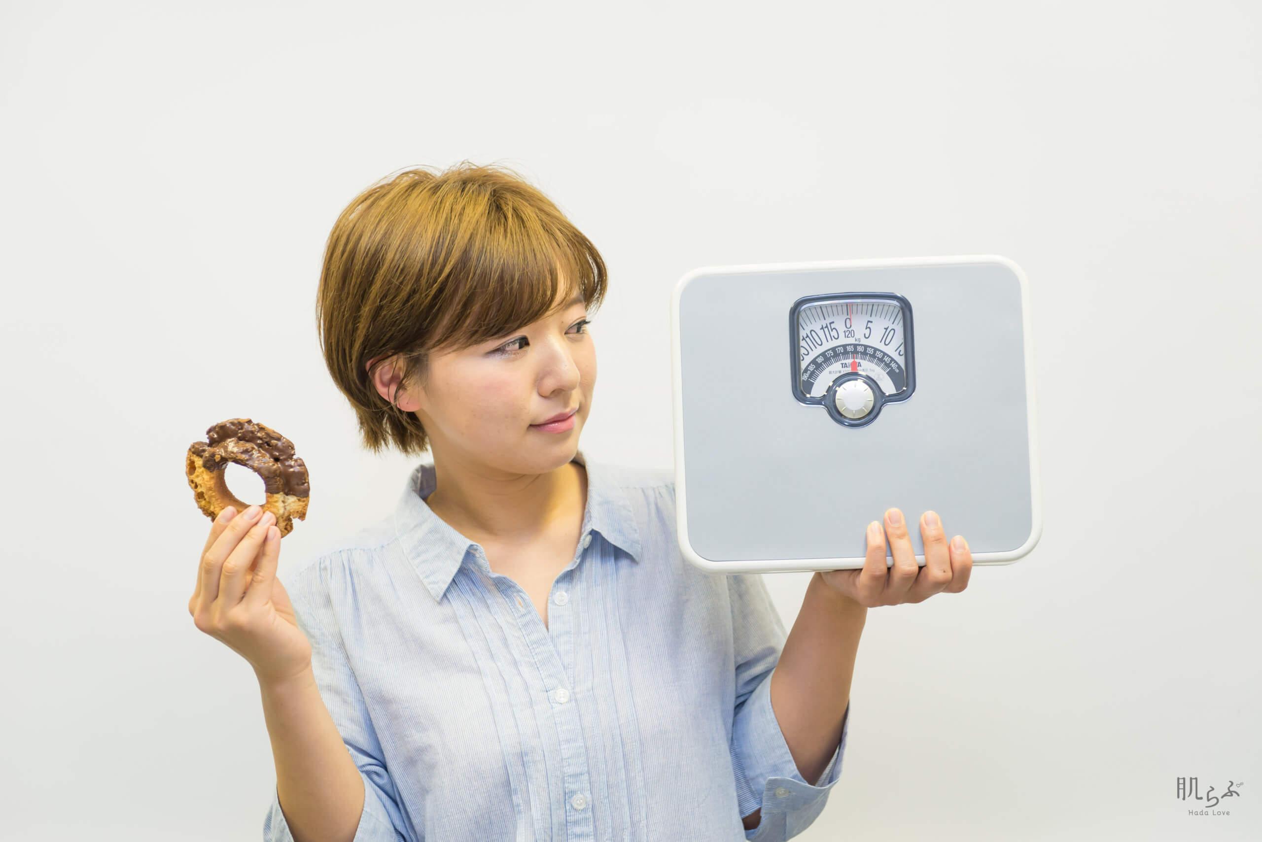 体重計とドーナツを持つ女性