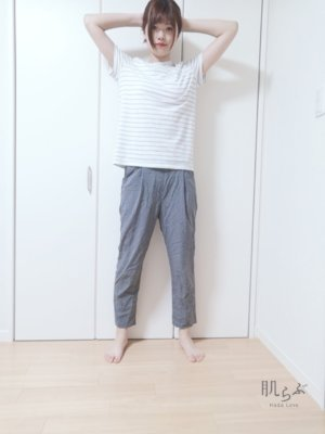 肩幅に脚を開いて立ち、手は頭の後ろで組む