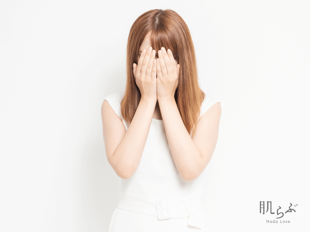 手で顔を覆っている女性